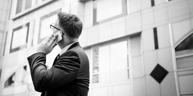 Geschäftsmann, der sprechendes telefon-konzept bearbeitet