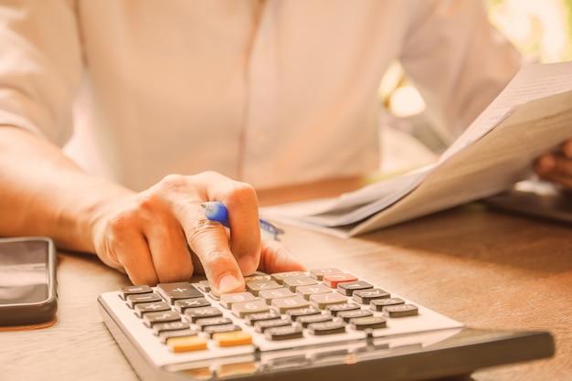 Geschäftsmann, der stift auf dokument hält, um buchhaltung mit rechner zu analysieren.