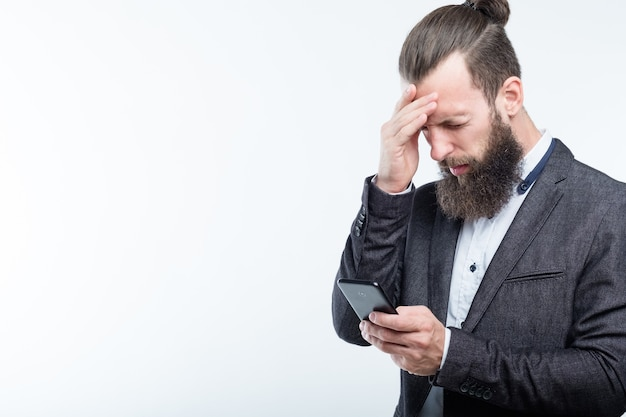 Geschäftsmann, der stirn berührt und telefon hält. kopfschmerzen müdigkeit und überarbeitung.