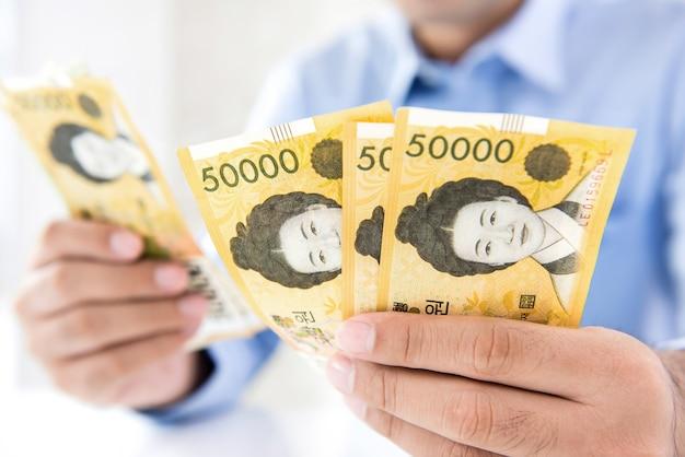 Geschäftsmann, der südkoreanische gewonnene banknoten des geldes in seinen händen zählt
