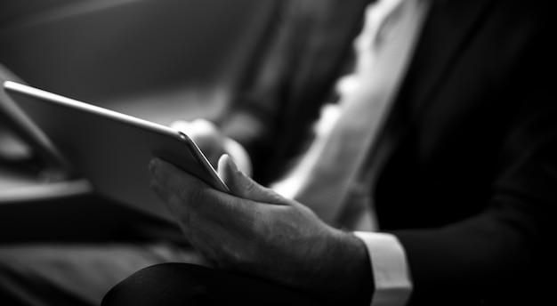 Geschäftsmann, der tablet-arbeitsauto nach innen verwendet