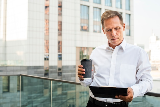 Geschäftsmann, der tablette beim halten des kaffees betrachtet