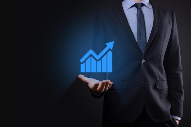 Geschäftsmann, der tablette hält und ein wachsendes virtuelles hologramm von statistik, grafik und diagramm mit pfeil oben auf dunklem hintergrund zeigt. aktienmarkt. geschäftswachstum, planung und strategiekonzept.