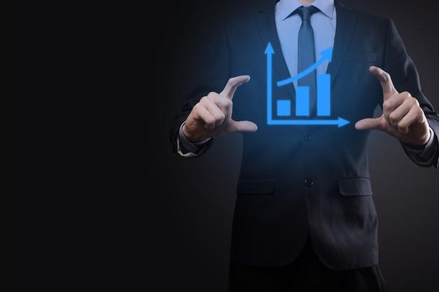 Geschäftsmann, der tablette hält und ein wachsendes virtuelles hologramm von statistik, grafik und diagramm mit pfeil oben auf dunklem hintergrund zeigt