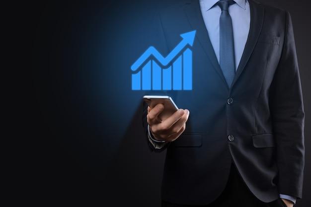 Geschäftsmann, der tablette hält und ein wachsendes virtuelles hologramm von statistiken, diagrammen und diagrammen mit pfeil nach oben auf dunklem hintergrund zeigt. aktienmarkt. geschäftswachstum, planung und strategiekonzept.