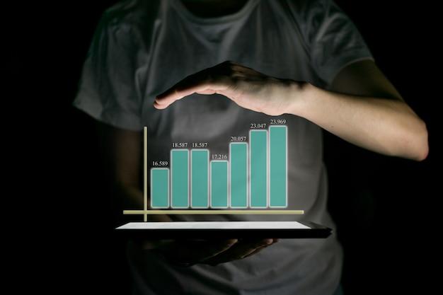 Geschäftsmann, der tablette hält und ein wachsendes virtuelles hologramm von statistiken zeigt