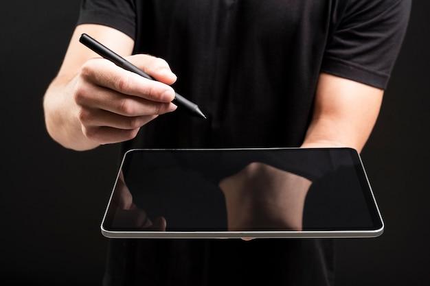 Geschäftsmann, der tablette hält und einen unsichtbaren bildschirm mit stift-social-media-abdeckung schreibt