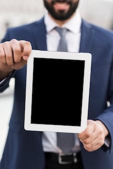 Geschäftsmann, der tablette hält