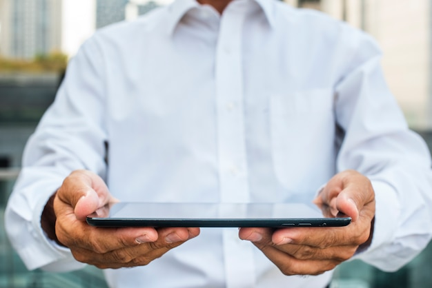 Geschäftsmann, der tablette in den händen hält