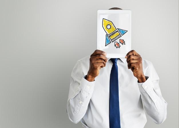 Geschäftsmann, der tablette mit raketenraumschiffikone hält