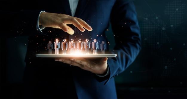 Geschäftsmann, der tablette und managementgruppe von personen in seiner hand hält.