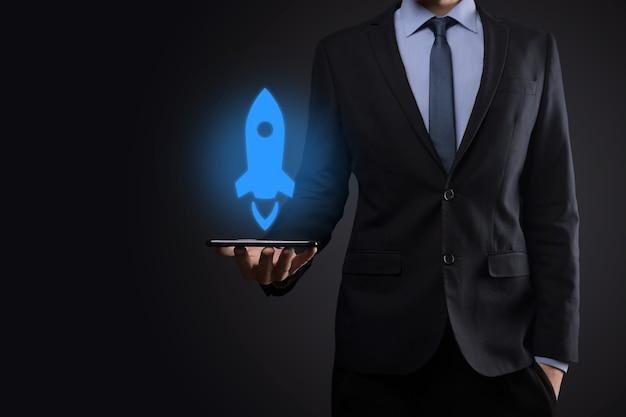 Geschäftsmann, der tablette und symbolrakete hält, startet und fliegt vom bildschirm heraus
