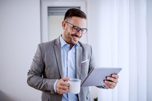 Geschäftsmann, der tablette verwendet und kaffee hält.