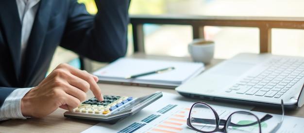 Geschäftsmann, der taschenrechner für analyse-mateting plan verwendet