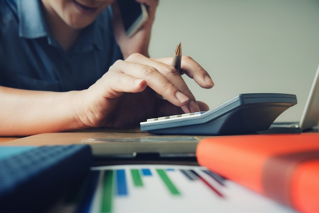 Geschäftsmann, der taschenrechner und smartphone zur berechnung des budgets und der finanzierung verwendet
