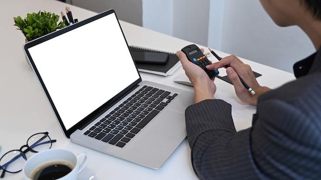 Geschäftsmann, der taschenrechner verwendet und mit laptop im büro arbeitet.