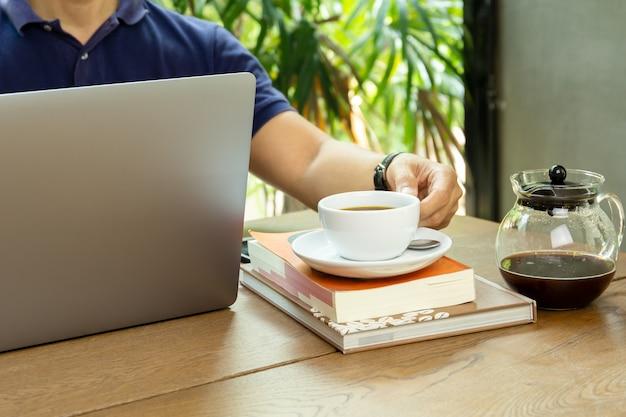 Geschäftsmann, der tasse kaffee beim arbeiten an laptop hält.