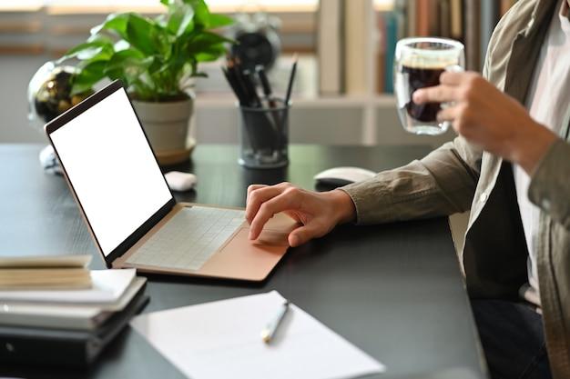 Geschäftsmann, der tasse kaffee hält und mit computerlaptop arbeitet.