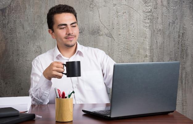 Geschäftsmann, der tasse tee hält und laptop am schreibtisch schaut.