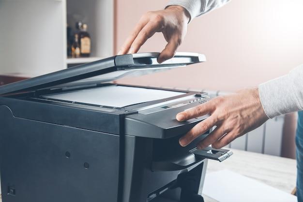 Geschäftsmann, der taste auf der tafel drückt, um fotokopierer zu verwenden