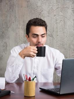 Geschäftsmann, der tee am schreibtisch trinkt.