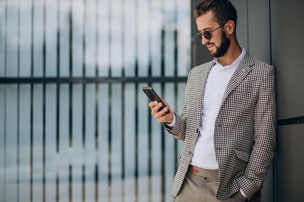 Geschäftsmann, der telefon außerhalb des bürozentrums benutzt