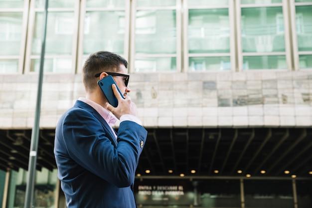 Geschäftsmann, der telefonanruf in der städtischen umwelt macht