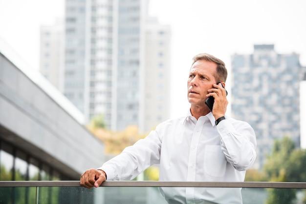 Geschäftsmann, der telefonisch sich bespricht