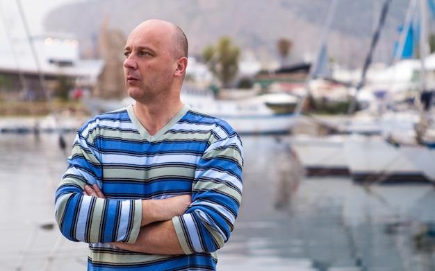 Geschäftsmann, der teure segelboote und yachten in einer küstenstadt bereitsteht