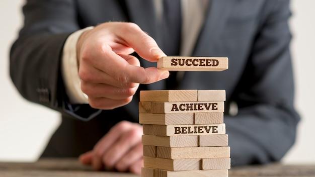 Geschäftsmann, der turm aus hölzernen dominosteinen mit motivationskonzeptzeichen glaubt, erreicht, erreicht und erfolgreich ist.