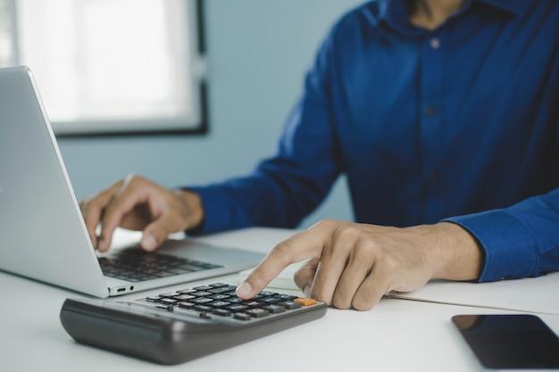 Geschäftsmann, der über finanzen auf laptop-computer mit taschenrechner arbeitet