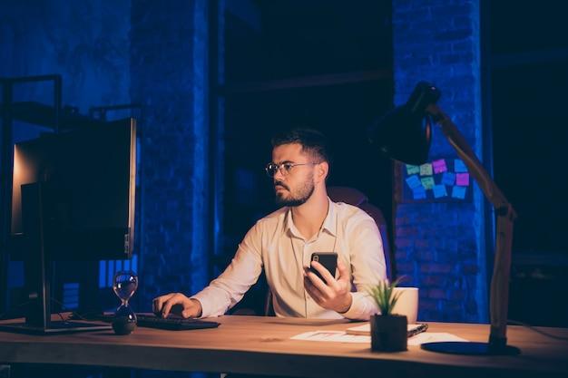 Geschäftsmann, der überstunden macht, hält telefon, das pc tippt