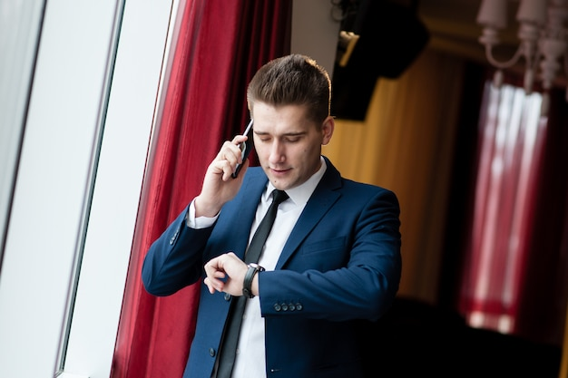 Geschäftsmann, der uhr betrachtet und am telefon spricht