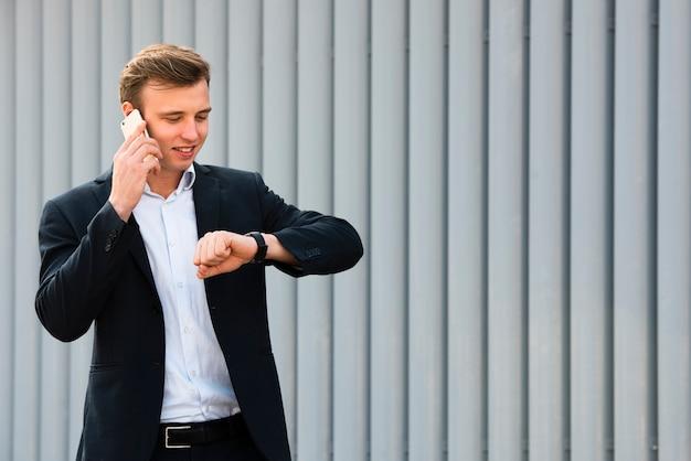Geschäftsmann, der uhr während am telefon betrachtet