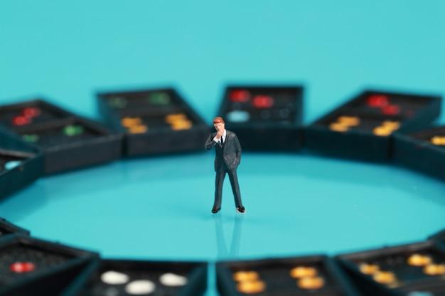 Geschäftsmann, der um domino schaut und etwas denkt