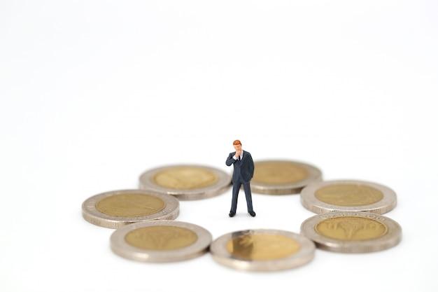 Geschäftsmann, der um münzen schaut und etwas denkt