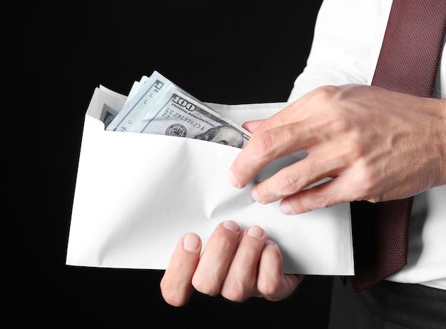 Geschäftsmann, der umschlag mit geld auf schwarzem hintergrund hält. korruptionskonzept