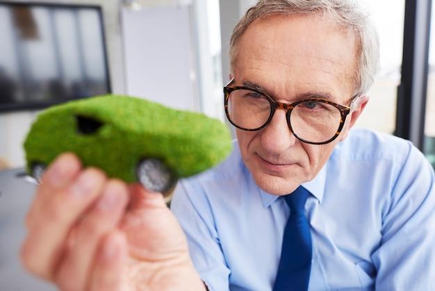 Geschäftsmann, der umweltfreundliches auto betrachtet