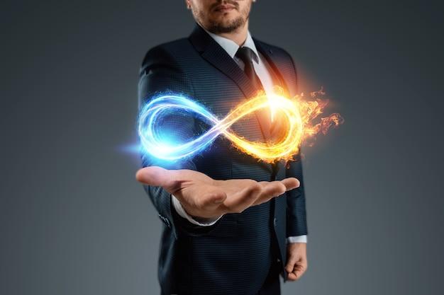 Geschäftsmann, der unendlichkeitssymbol, feuereissymbol zeigt