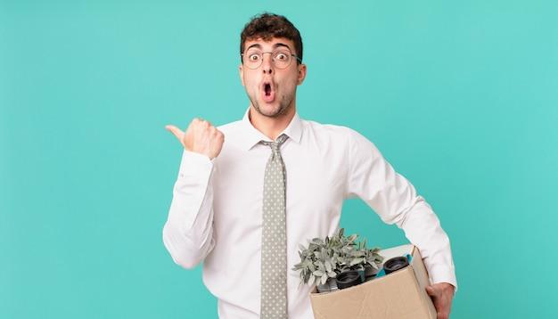 Geschäftsmann, der ungläubig ausschaut, auf das objekt an der seite zeigt und sagt, wow, unglaublich. kündigungskonzept