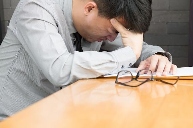 Geschäftsmann, der unter kopfschmerzen bei der arbeit leidet