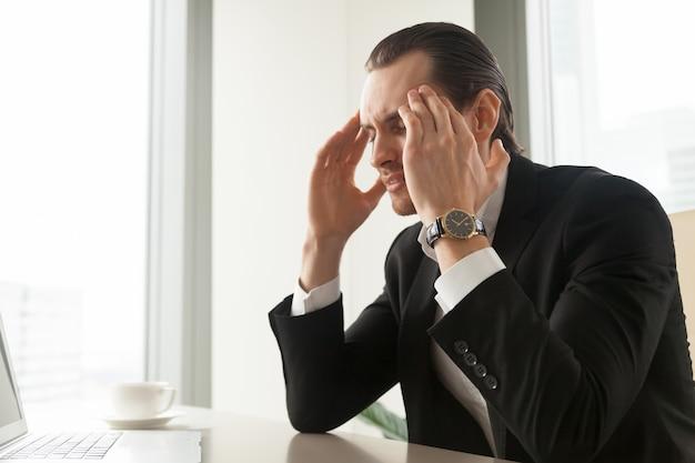 Geschäftsmann, der unter migräne oder kopfschmerzen leidet