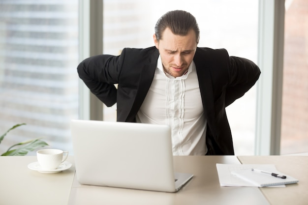 Geschäftsmann, der unter rückenschmerzen am arbeitsplatz leidet
