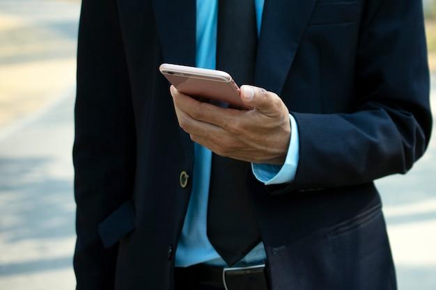 Geschäftsmann, der unter verwendung des intelligenten mobiltelefons hält