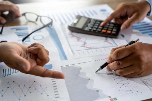 Geschäftsmann, der unter verwendung einer taschenrechnerfinanzbuchhaltungs-konzeptleistung arbeitet, um behilfliche buchhaltung des mannes zu balancieren