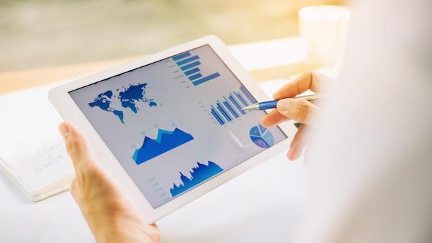 Geschäftsmann, der unternehmensfinanzbericht-bilanzauszug mit dokumentengraphiken auf intelligentem gerät analysiert.
