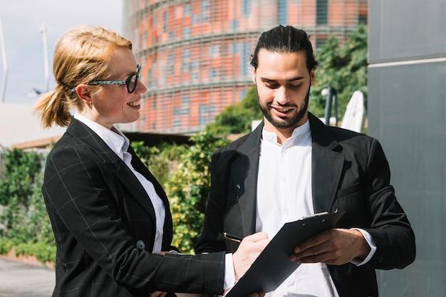 Geschäftsmann, der unterschrift auf dokument von der geschäftsfrau an draußen nimmt