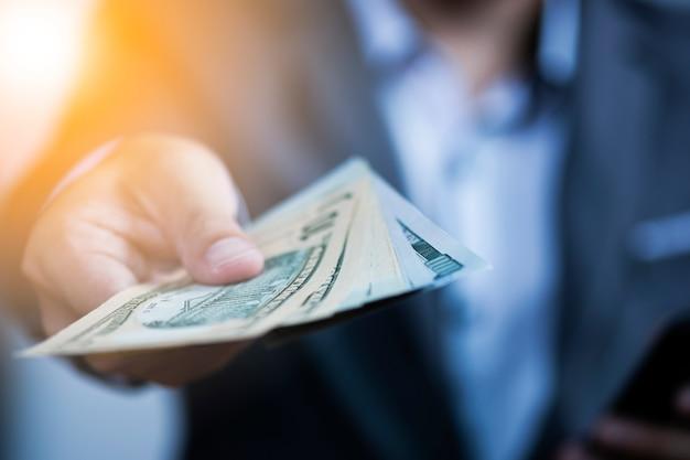 Geschäftsmann, der usd-banknote für zahlung hält.