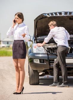 Geschäftsmann, der versucht, sein defektes auto zu reparieren.