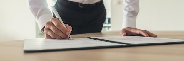 Geschäftsmann, der vertrag unterzeichnet